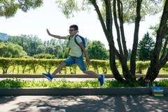 De schooljongen sprong voor vreugde in het park dat de lessen beëindigden stock afbeelding