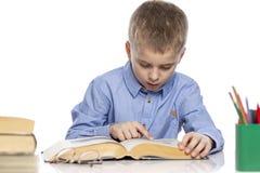 De schooljongen zit bij de lijst en doet zijn thuiswerk Ge?soleerd op een witte achtergrond stock afbeeldingen