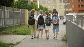 De schoolkinderen, jongens en meisjes, gaan naar school met rugzakken Achter mening Terug naar school, kennisdag stock footage