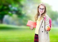 De schoolleeftijd van het kindmeisje met het concept van het appelonderwijs stock foto's