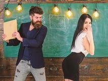 De schoolmeester straft sexy student met het meppen op haar billen met boek Leraar die meisje in klaslokaal slaan Mens die met stock afbeeldingen