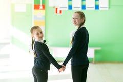De schoolmeisjemeisjes gaan hand in hand royalty-vrije stock afbeeldingen