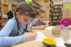 De schoolmeisjes in buitenschoolse activiteiten trekken in de bibliotheek stock fotografie