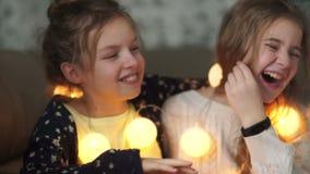 De schoolmeisjes hebben thuis een pyjamapartij en aandeelgeheimen Meisje die in het oor van haar zuster, allebei fluisteren die m stock videobeelden