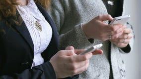 De schoolmeisjes houden slimme telefoons binnen in handen stock videobeelden