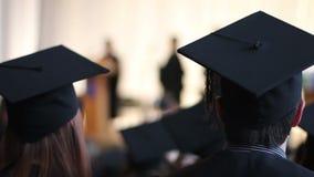 De schoolstudenten letten deken het schudden op de hand van de gediplomeerde op stadium Vrolijk applaus stock videobeelden