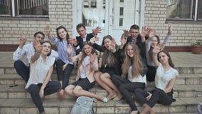 De schoolstudenten zitten op de stappen van de school en golven hun handen Groep Middelbare schoolstudenten die buiten zitten stock footage