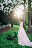 De schoonheid van aard en vrouwen, meisje in lange kleding op de het plaatsen zon onder de witte tot bloei komende Apple-bomen, royalty-vrije stock fotografie