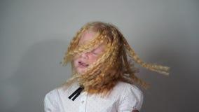 De schoonheid van langzame motie - het Schoolmeisje met haar haarplooiing schudt haar hoofd op een grijze achtergrond stock videobeelden