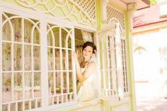 De schoonheidsbruid in bruids toga met boeket en het kant versluieren op de aard Mooi modelmeisje in een witte huwelijkskleding Stock Foto's