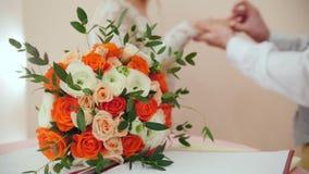 De schoonheidsbruid en de knappe bruidegom dragen gouden ringen elkaar voor huwelijksboeket Huwelijksceremonie stock videobeelden