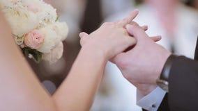 De schoonheidsbruid en de knappe bruidegom dragen ringen elkaar stock video