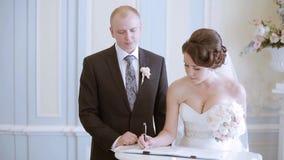 De schoonheidsbruid en de knappe bruidegom registreren het huwelijk stock video