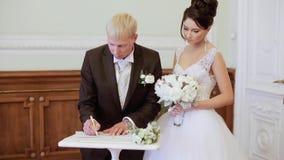 De schoonheidsbruid en de knappe bruidegom registreren het huwelijk stock videobeelden