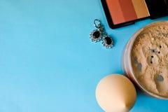 De schoonheidsdoos, los steen mineraal poeder en bloost met een schoonheidsmixer voor make-up en zilveren oorringen op een blauwe stock foto