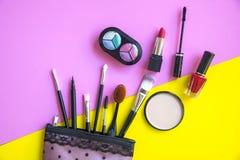 De schoonheidsmiddelen en de manierachtergrond met maken omhoog kunstenaarsvoorwerpen: lippenstift, oogschaduwwen, mascara, eyeli Stock Foto's