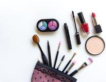 De schoonheidsmiddelen en de manierachtergrond met maken omhoog kunstenaarsvoorwerpen: lippenstift, oogschaduwwen, mascara, eyeli Stock Fotografie