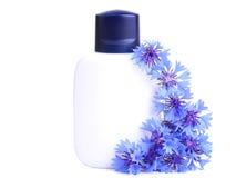 De schoonheidsmiddelenfles behandelde blauwe bloemen op wit royalty-vrije stock foto's