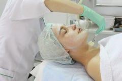 In de schoonheidssalon doet een jonge vrouw een schil op haar gezicht stock afbeeldingen