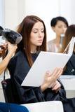 De schoonheidsspecialist doet haarstijl voor vrouw in herenkapper Royalty-vrije Stock Fotografie