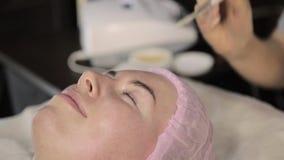 De schoonheidsspecialist doet rf-gezicht het opheffen procedure voor een vrouw in een schoonheidszaal De hardwarekosmetiek stock videobeelden