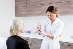 De schoonheidsspecialist duwt een spuit om Botox in te spuiten stock foto