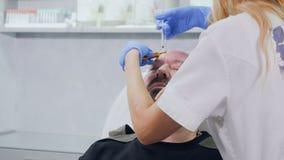 De schoonheidsspecialist maakt botox injectie voor homosexueel in schoonheidskliniek stock video
