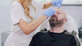 De schoonheidsspecialist maakt botox tot injectie in voorhoofd aan homosexueel stock footage