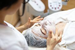 De schoonheidsspecialist maakt een gezichtsbehandeling in kuuroord Vrouw in masker op gezicht in kuuroordsalon royalty-vrije stock fotografie