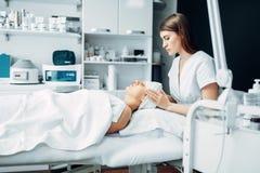 De schoonheidsspecialist maakt gezichts tot massage aan vrouwelijke patiënt royalty-vrije stock afbeelding