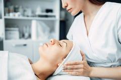 De schoonheidsspecialist maakt gezichts tot massage aan vrouwelijke patiënt royalty-vrije stock foto