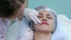 De schoonheidsspecialist maakt tot injectie plastic lippen stock videobeelden