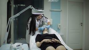 De schoonheidsspecialist maakt tot injectie plastic lippen Jonge vrouw op lippenvergroting in een kliniek stock video
