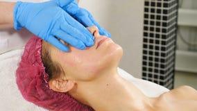De schoonheidsspecialist masseert vrouwelijke cliënt de schoonheidstherapeut bereidt vrouwengezicht voor behandeling in salon voo stock videobeelden