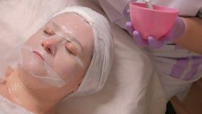 De schoonheidsspecialist met behulp van een witte borstel past het gel door een masker op het vrouwelijke gezicht in een schoonhe stock video