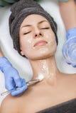 De schoonheidsspecialist past gezichtsmasker met borstel op jonge vrouw in Kuuroord toe sa stock foto