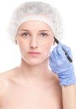 De schoonheidsspecialist trekt correctielijnen op vrouwengezicht stock foto's