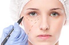 De schoonheidsspecialist trekt correctielijnen op vrouwengezicht Royalty-vrije Stock Foto