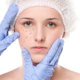 De schoonheidsspecialist trekt correctielijnen op vrouwengezicht stock foto
