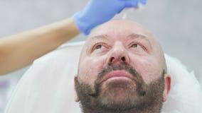 De schoonheidsspecialist veegt bloed van voorhoofd na botoxinjectie af stock video