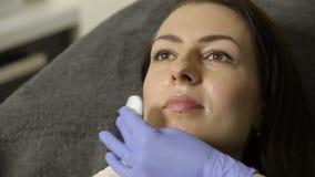De schoonheidsspecialist veegt gezicht van vrouwelijke patiënt met katoenen Spons vóór procedure af desinfectie stock videobeelden