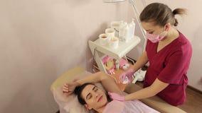 De schoonheidsspecialist verwijdert het haar uit het meisje op de oksels Het zoeten in de salon stock video