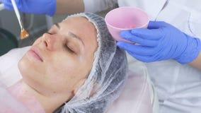 De schoonheidsspecialist zet een masker op het gezicht van de vrouw met een borstel Handen van een cosmetologist in blauwe rubber stock videobeelden