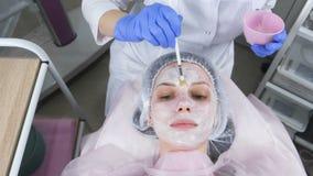 De schoonheidsspecialist zet een wit masker op het gezicht van de vrouw met een borstel Handen van een cosmetologist in blauwe ru stock videobeelden