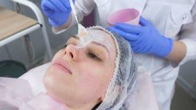 De schoonheidsspecialist zet een wit masker op het gezicht van de vrouw met een borstel Handen van een cosmetologist in blauwe ru stock footage