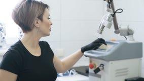 De schoonheidsspecialist zet elektronisch apparaat vóór kosmetische procedure, langzame motie aan stock videobeelden