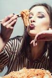 De schoonheidsvrouw heeft deegwaren voor diner Het schoonheidsmodel eet spaghetti met eetstokjes stock afbeeldingen