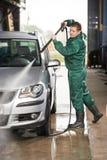 De schoonmakende auto van de arbeider met gedrukt water stock foto