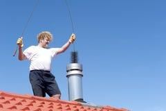 De schoonmakende schoorsteen van de mens op betegeld dak Stock Fotografie