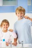De schoonmakende tanden van de jongen en van het meisje in badkamers stock foto's